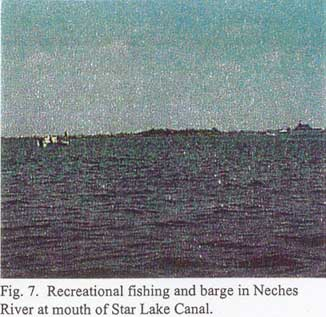 Recreational fishing and barge in Neches River at mouth of Star Lake Canal