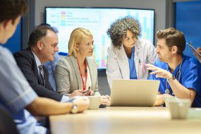 Group of professionals in discussion with a computer