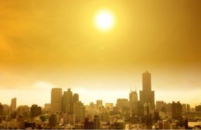 A bright sun with smog and haze beats down on a large city.