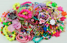 A large pile of children's toy jewelry - beads, bracelets and charms