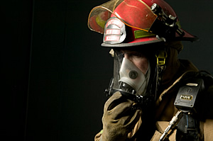 Firefighter uses a full-face respirator.