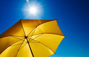 Looking up at the bright sun and blue sky from under a bright yellow beach umbrella.