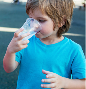 Boy wearing a blue t-shirt drinking water from a plastic cup