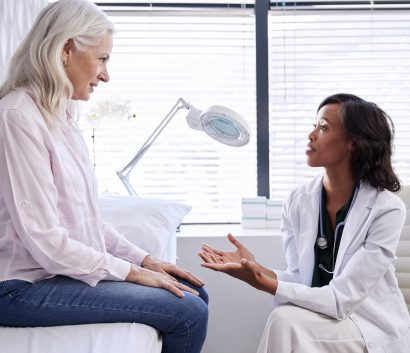 Mature Woman In Consultation With Female Doctor Sitting On Examination Couch In Office