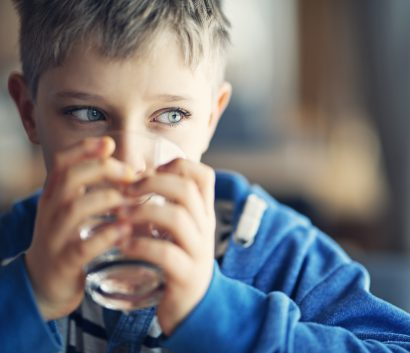 Portrait of a little boy drinking a glass of water