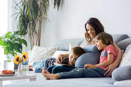 Young pregnant woman, reading book at home to her boys