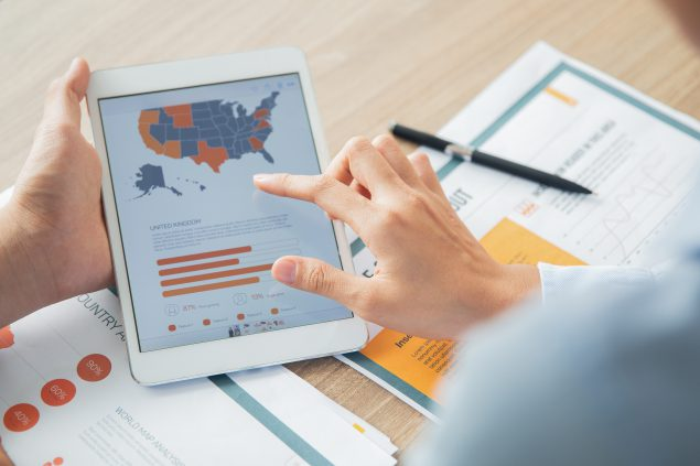 Person at a desk holding a tablet that has a map of the United States and a bar graph.
