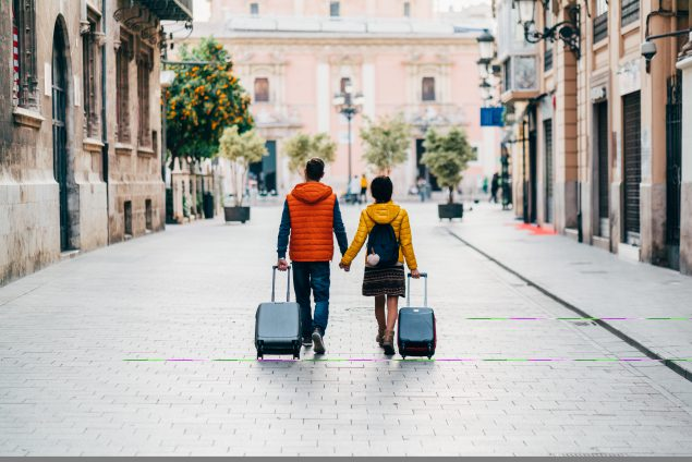 Couple walking with suitcases.