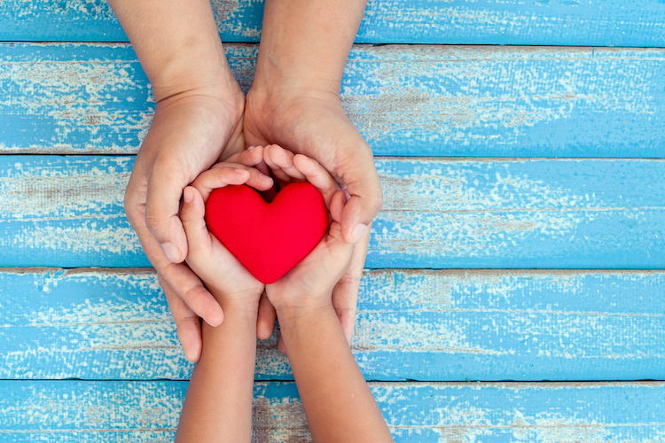 Image of adult and child hands holding a red heart.