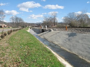 East draining ditch from the former PCB production facility (paved during PCB clean-up efforts in late 1990s).
